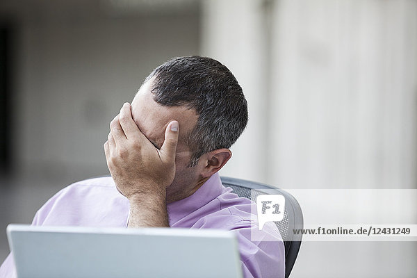 A Caucasian businessman pondering a problem while working on a laptop computer.