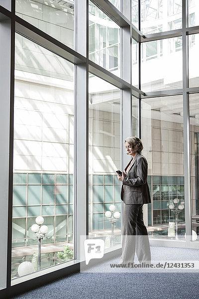 Eine kaukasische Geschäftsfrau  die neben einem großen Fenster in der Lobby eines Kongresszentrums steht und ihr Mobiltelefon auf Nachrichten überprüft.