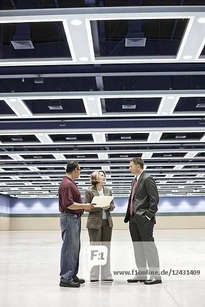 Drei Planer von Geschäftstreffen sprechen auf dem Boden eines Kongresszentrums.