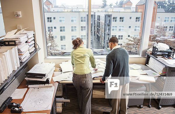 A view from behind of two people going over plans for a new space in their office.