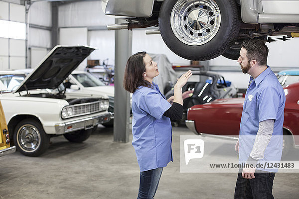 Two Caucasian male and female car mechanics at work on a car in a classic car repair shop.