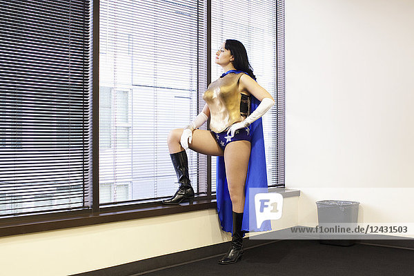 A Caucasian woman office super hero stands at a window pondering her next move.