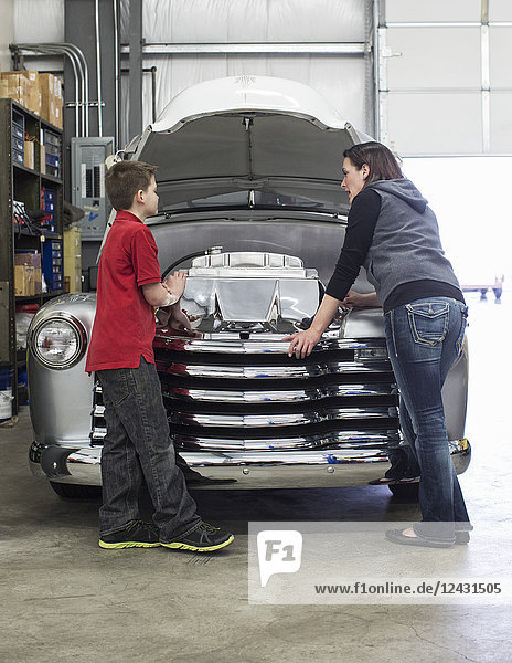 A Caucasian female car mechanic talks to her young son about a car engine in a classic car repair shop.