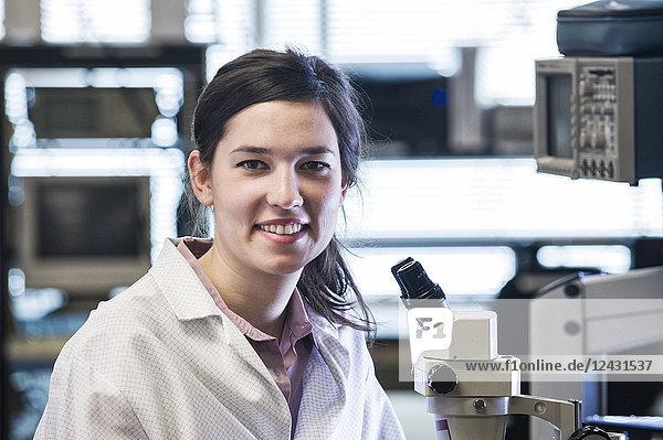 Das Porträt einer Technikerin am Mikroskop in einer technischen Forschungs- und Entwicklungsstätte.