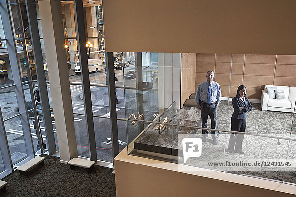 A large building  lobby  view looking into an office with glass walls  two business people talking.
