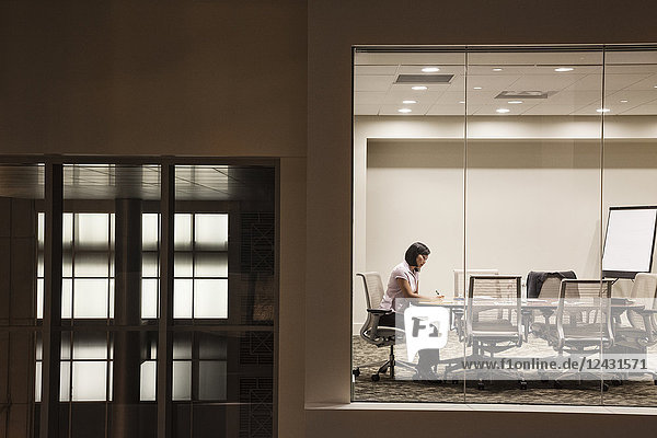 A view looking into a conference room at night of an Asian businesswoman.