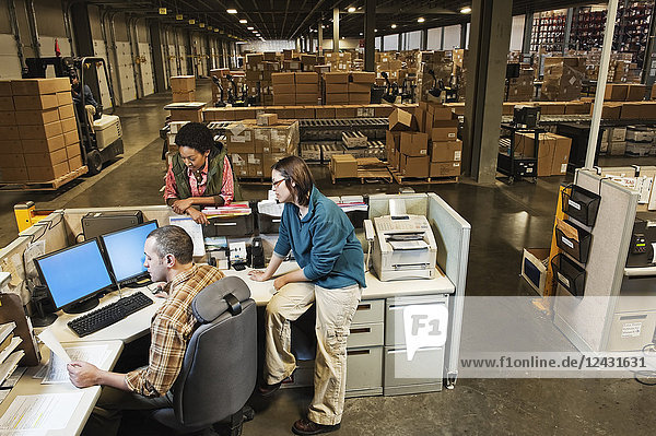 Three mixed race warehouse workers studying a document on a computer at the front desk of a distribution warehouse.