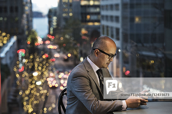 A side view of an Asian businessman sitting at a table working on his phone in front of a window with a view to a city street at dusk.