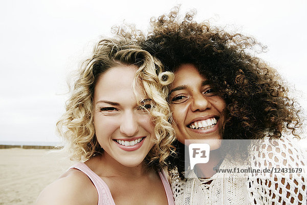 Portrait of two smiling young women with blond and brown curly hair standing on sandy beach  looking at camera.