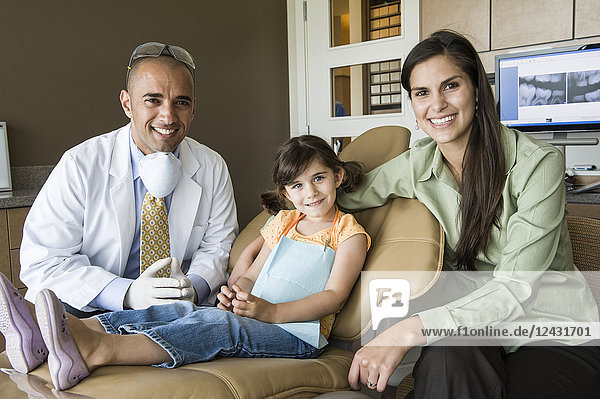 A portrait of a Middle Eastern male dentist a female child patient and her mom in a dental office.