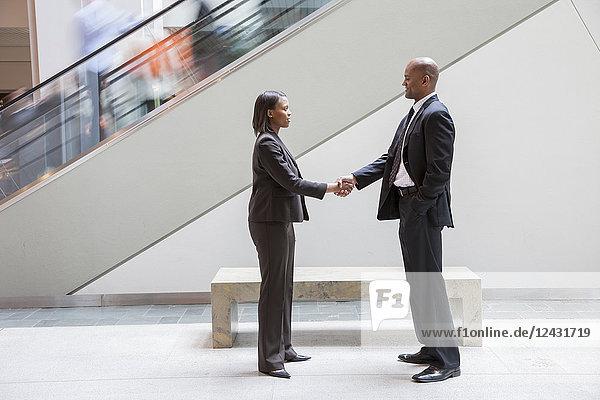 Eine schwarze Geschäftsfrau schüttelt einem schwarzen Geschäftsmann  der neben einer Rolltreppe in einem Kongresszentrum steht  die Hand.