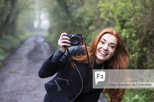 Smiling young woman with long red hair walking along forest path  taking pictures with vintage camera.