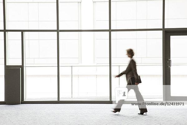 Eine Geschäftsfrau verschwimmt in ihrer Silhouette  während sie an einem großen Fenster des Kongresszentrums vorbeigeht.