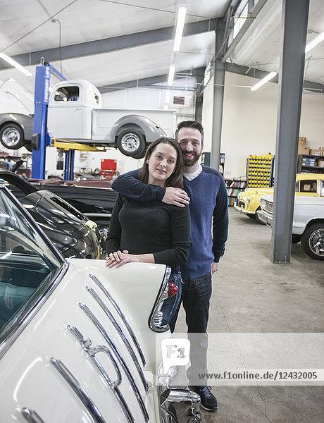 Ein Ehepaar  Mechaniker  die in einer Oldtimer-Autowerkstatt arbeiten. Mann und Frau.