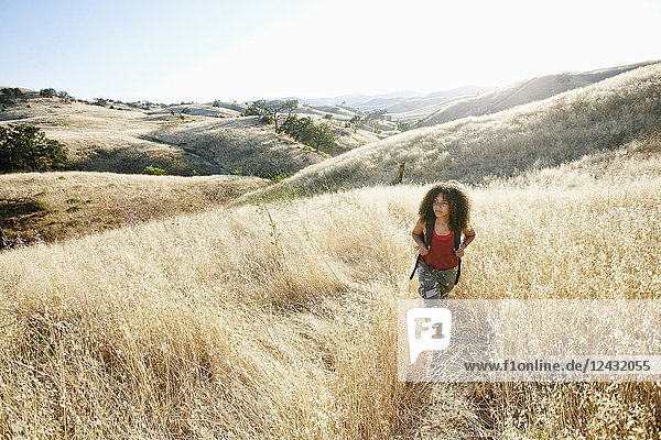 Young woman with curly brown hair hiking in urban park.