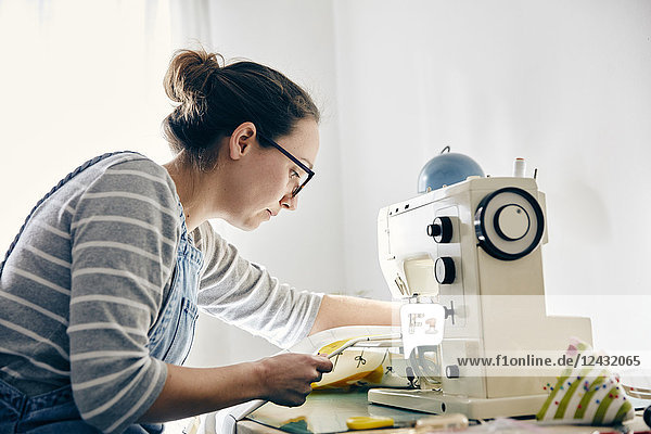 Woman using electric sewing machine to make curtains