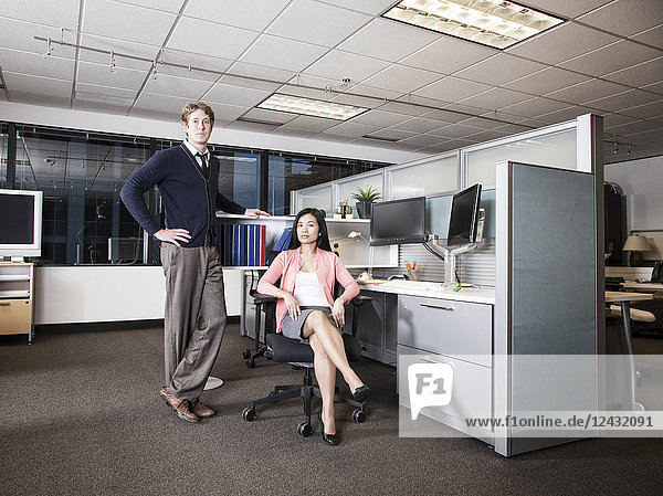 Caucasian businessman and Asian businesswoman team of people in a cubicle office space.