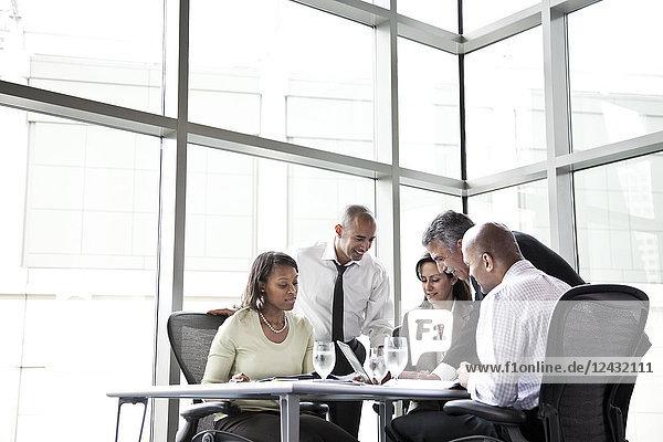 Eine gemischtrassige Gruppe von männlichen und weiblichen Geschäftsleuten bei einem Treffen an einem Konferenztisch neben einem großen Fenster in einem Kongresszentrum.