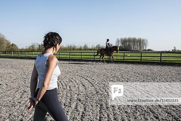 Trainerin beobachtet ein junges Mädchen  das auf einem braunen Pferd auf der Koppel reitet.