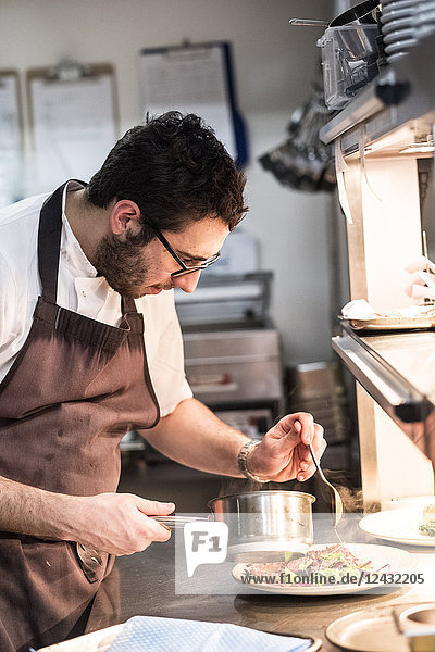 Bearded chef wearing glasses and apron standing in commercial kitchen at counter  plating food.