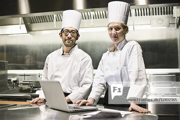 A portrait of a mixed race pair of chefs working with a laptop computer in a commercial kitchen.