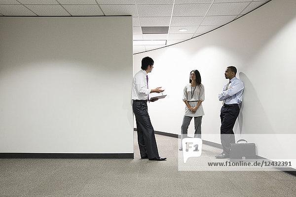 Eine gemischtrassige Gruppe von drei Geschäftsleuten  die in einem Büroflur stehen und reden.