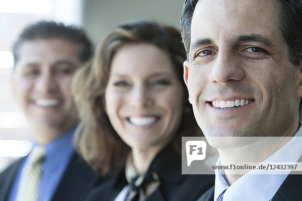 A closeup portrait of a row of multi ethnic business people  with focus on the Caucasian businessman.