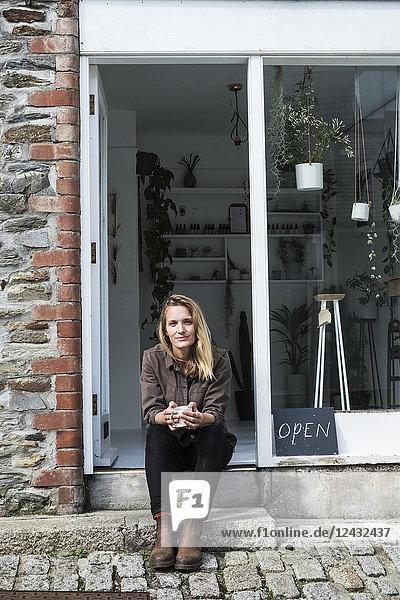 Lächelnde Besitzerin eines Pflanzenladens sitzt auf der Treppe vor ihrem Laden und schaut in die Kamera.