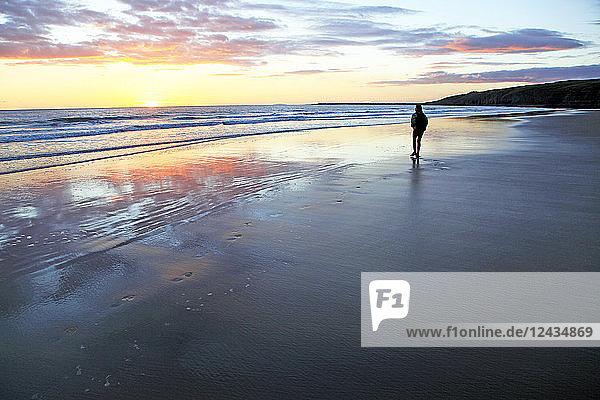 A woman walks on Southerndown beach  Ogmore  South Wales  United Kingdom  Europe
