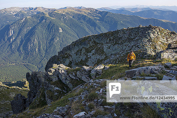 A hiker climbs along a high ridge near Maliovitsa in the Rila Mountains with distant views of valleys and hills  Bulgaria  Europe