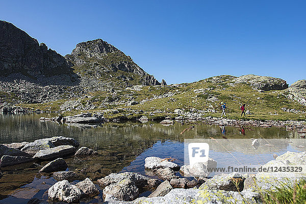 Hiking next to the clear water of Elenino Lake near Maliovitsa in the Rila Mountains  Bulgaria  Europe