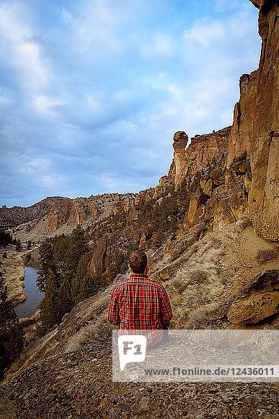 Man wearing a flannel shirt looking at a large rock formation  Oregon  United States of America  North America