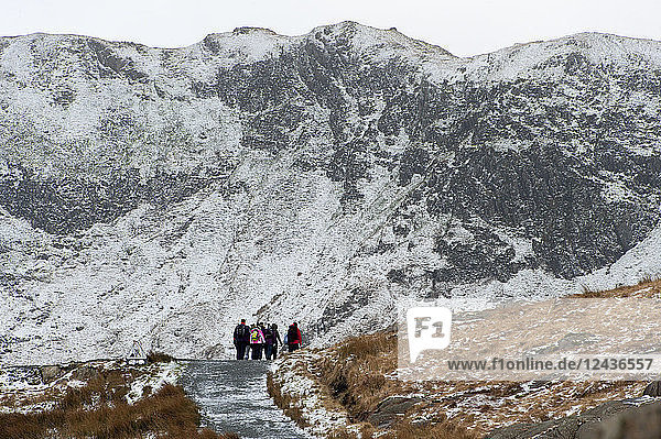 Hikers on the Miner's Track at base of Mount Snowdon in a wintry landscape in the Snowdonia National Park  Gwynedd  Wales  United Kingdom  Europe