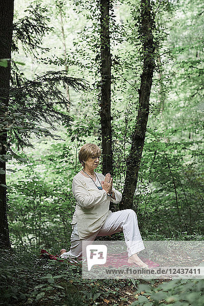 Senior woman doing yoga in the forest