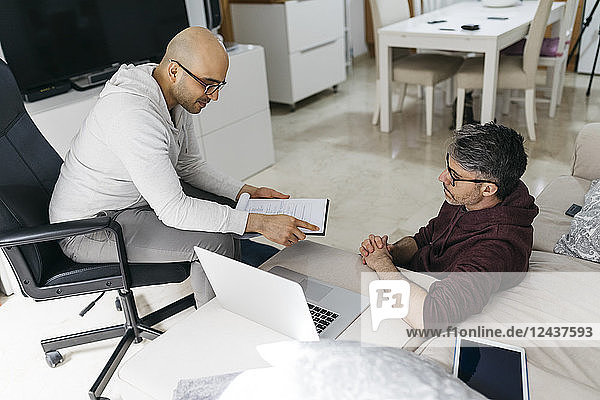 Two colleagues working on documents and laptop at home