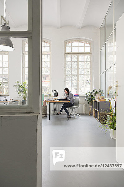 Woman working at desk in a loft office