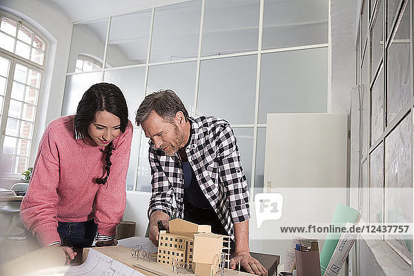 Colleagues discussing architectural model in office