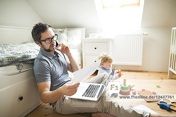 Father with his little son working from home