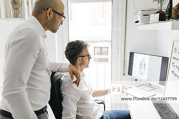 Two colleagues working on desktop pc at home