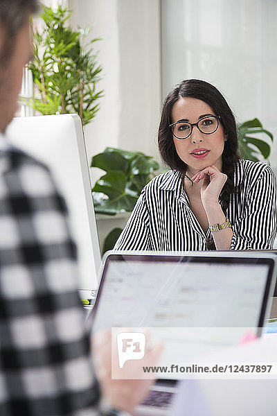 Portrait of woman with colleague working at desk in office