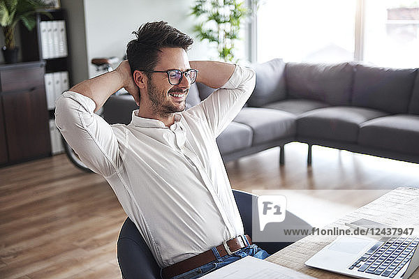 Content businessman sitting at desk at home office