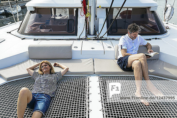 Mature woman relaxing on catamaran trampoline  while husband is reading a book