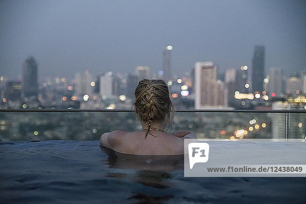 Thailand  Bangkok  back view of woman bathing in Infinity Pool looking at skyline
