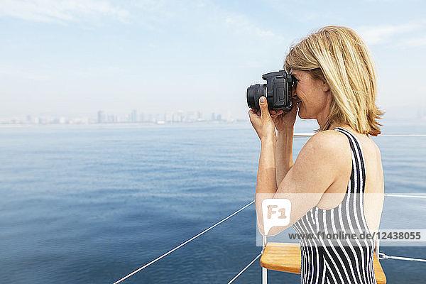 Mature woman on sailing trip photographing skyline of Barcelona