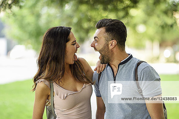 Couple looking at each other pulling funny faces