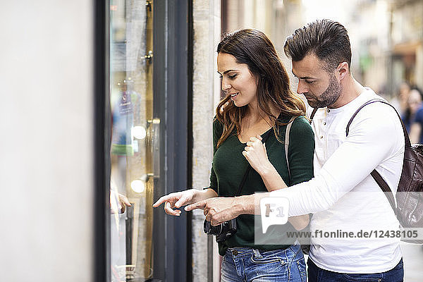 Couple looking at shop window in the city