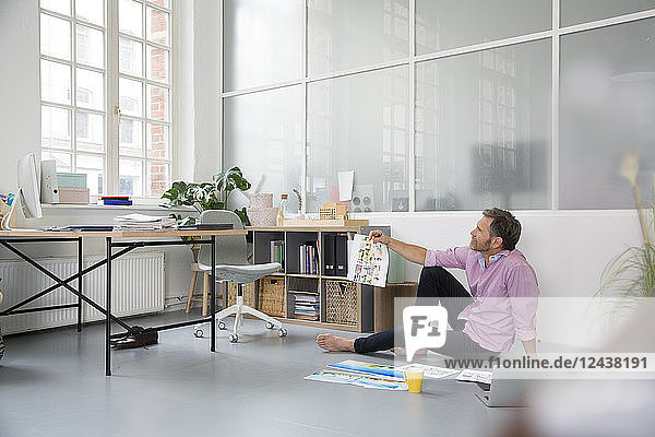 Casual man with plans and laptop sitting on the floor in a loft office