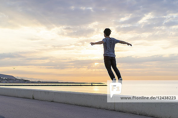 Young Chinese man jumping on wall at the beach
