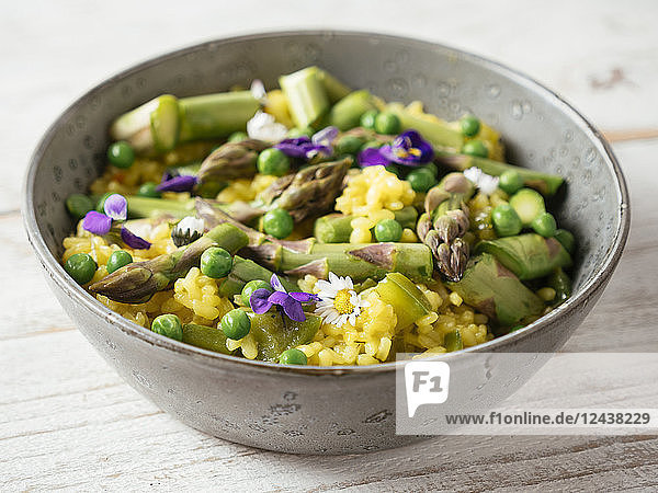 Risotto with green asparagus and peas  garnished with edible flowers Risotto with green asparagus and peas, garnished with edible flowers