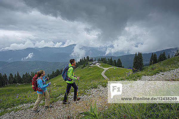 Germany  Lenggries  young couple with hiking poles hiking upwards